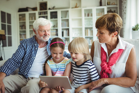Grandchildren using digital tablet with their grandparents at home Stock Photo