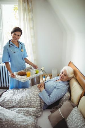 Portrait of nurse serving breakfast to senior woman in bedroom