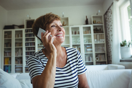 ageing process: Senior woman talking on mobile phone in living room at home
