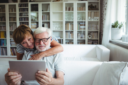 Senior couple using digital tablet in living room