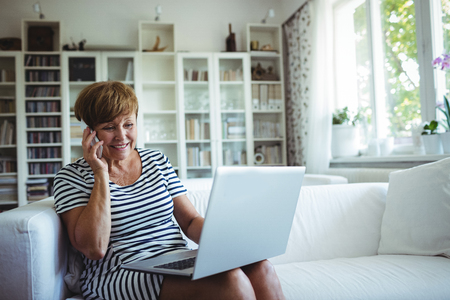 年配の女性が自宅の居間でノート パソコンを使用しながら携帯電話で話しています。 写真素材