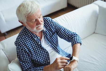 ageing process: Senior man adjusting a time on smartwatch in living room at home Stock Photo