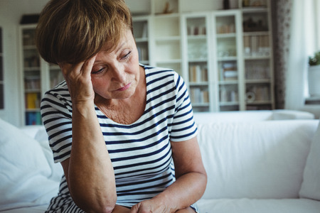 Tense woman sitting on sofa in living room at home