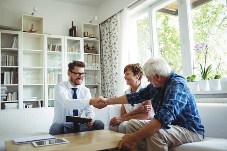 hands work: Financial advisor shaking hands with senior man in living room
