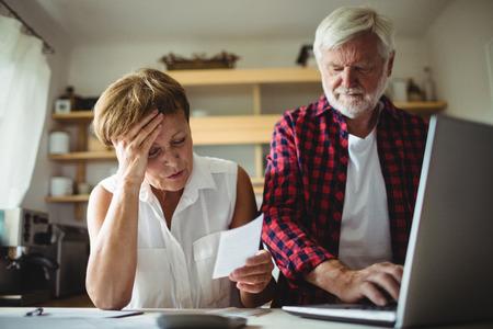 Senior couple de payer des factures en ligne sur un ordinateur portable à la maison Banque d'images - 65507001