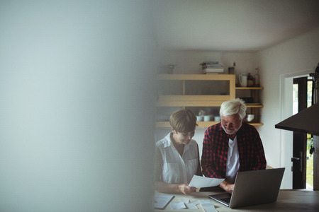Senior couple paying bills online on laptop at home