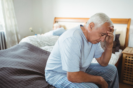 unhappy man: Frustrated senior man sitting on bed in bedroom