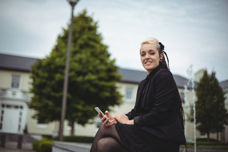 attractive  female: Portrait of businesswoman holding mobile phone in office campus Stock Photo