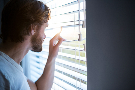 looking through window: Man looking through window blinds after waking up at home