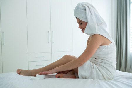Woman applying moisturizer cream on her leg in bedroom at home Stock Photo