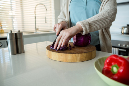 Mid section of woman cutting red cabbage in kitchen at home
