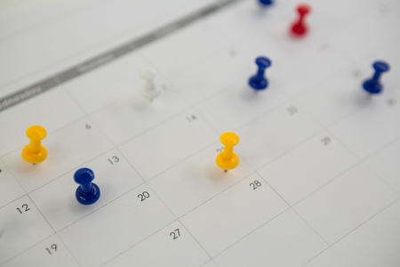 Close-up of blue, red and yellow push pin marked on calendar Stock Photo