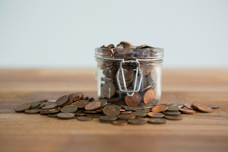 secure growth: Close-up of coins in jar on table
