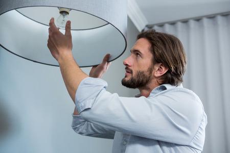 L'uomo che installa una lampadina in salotto a casa Archivio Fotografico - 65497170