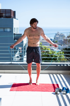 Man exercising with skipping ropes in balcony at home Stock Photo