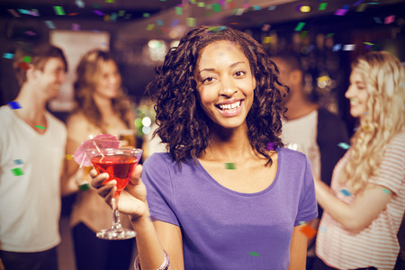 Portrait of smiling girl having cocktail with her friends against flying colours Stock Photo