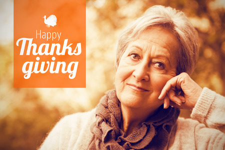 Thanksgiving greeting text against senior woman in the park Stock Photo
