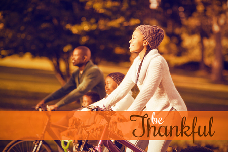 weekend activities: Thanksgiving greeting text against side view of a young family doing a bike ride Stock Photo