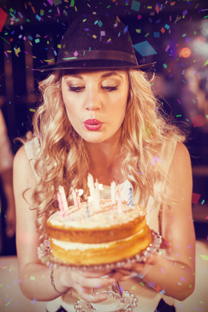 Woman blowing out candles against flying colours