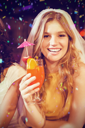 Pretty girl with cocktail against flying colours Stock Photo