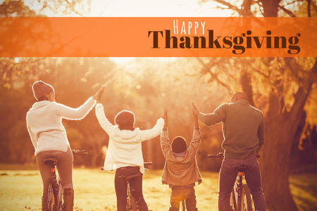 Digitally generated image of happy thanksgiving text against rear view of a young family with arms raised on bike
