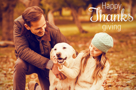 weekend activities: Thanksgiving greeting text against young family with a dog Stock Photo