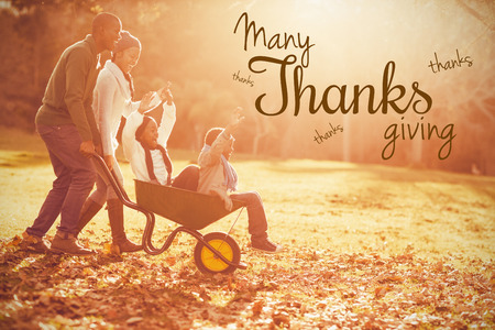 weekend activities: Happy thanksgiving day message against young parents holding their children in a wheelbarrow Stock Photo
