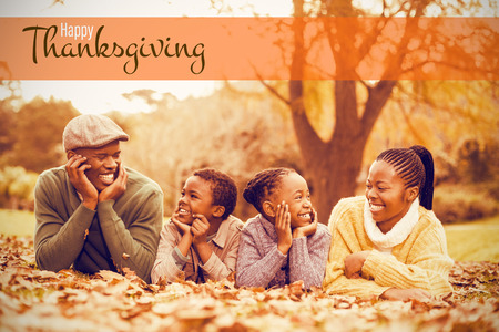 Illustration of happy thanksgiving day text greeting against portrait of a young smiling family lying in leaves