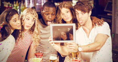 Friends taking selfie with tablet against flying colours