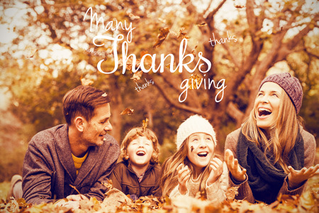weekend activities: Happy thanksgiving day message against smiling young family throwing leaves around