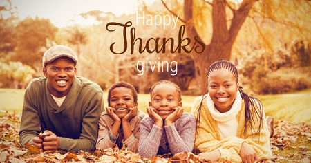 weekend activities: Thanksgiving greeting text against portrait of a young smiling family lying in leaves Stock Photo