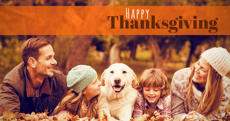 girl lying studio: Digitally generated image of happy thanksgiving text against young family with a dog