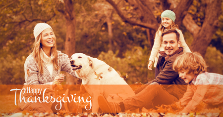 Illustration of happy thanksgiving day text greeting against young family with a dog in leaves