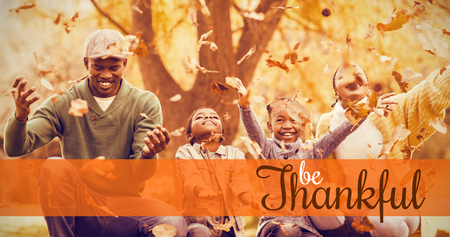 Thanksgiving greeting text against young smiling family throwing leaves around