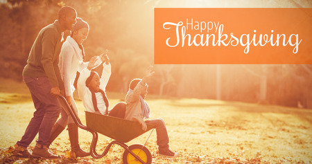 weekend activities: Thanksgiving greeting text against young parents holding their children in a wheelbarrow