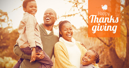 weekend activities: Thanksgiving greeting text against portrait of a smiling young family laughing Stock Photo