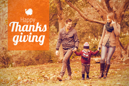Thanksgiving greeting text against smiling young family walking together Stock Photo