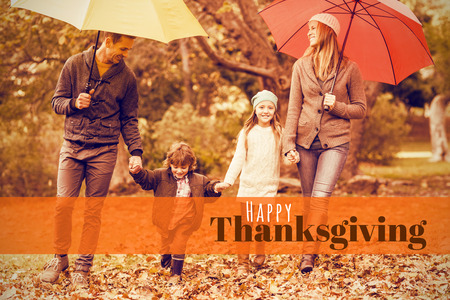 Digitally generated image of happy thanksgiving text against smiling young family under umbrella Stock Photo