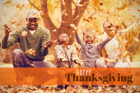 weekend activities: Digitally generated image of happy thanksgiving text against young smiling family throwing leaves around
