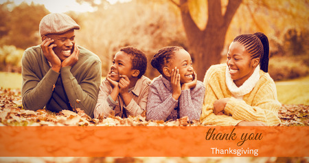 girl lying studio: Thanksgiving greeting text against portrait of a young smiling family lying in leaves Stock Photo