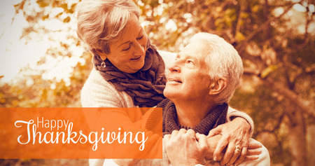 Senior couple in the park against thanksgiving greeting text
