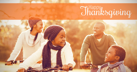 Thanksgiving greeting text against young smiling family doing a bike ride