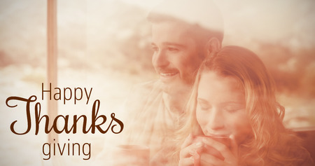 Thoughtful couple with coffee cups seen through cabin window against thanksgiving greeting text Stock Photo