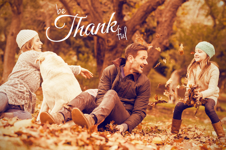 Digital image of happy thanksgiving day text greeting against young family with a dog in leaves Stock Photo