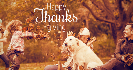 Thanksgiving greeting text against young family with a dog in leaves Stock Photo