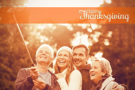 weekend activities: Thanksgiving greeting text against smiling small family taking selfies Stock Photo