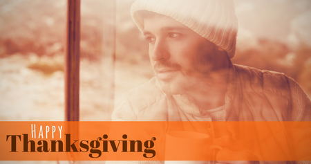 man looking out: Digitally generated image of happy thanksgiving text against thoughtful man with cup looking out through window Stock Photo