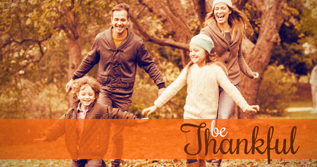 weekend activities: Thanksgiving greeting text against smiling young family running into leaves