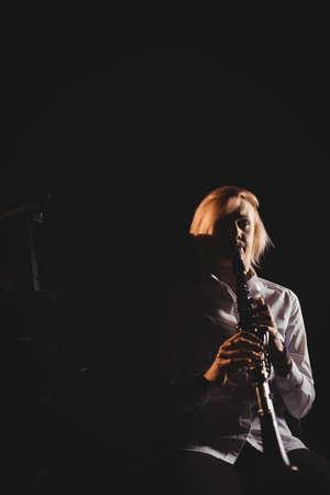clarinete: Estudiante femenino tocando el clarinete en un estudio LANG_EVOIMAGES