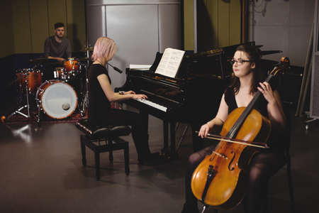 drum set: Group of students playing double bass, drum set and piano in a studio